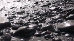 Waves crashing on large pebbles and stones - stock footage