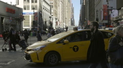 Taxi cab turning on busy intersection in Midtown Manhattan people crossing NYC Stock Footage