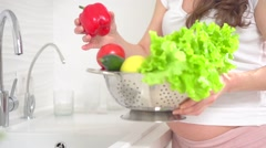 Beautiful Young Pregnant Woman Washing fresh organic Vegetables in the Kitchen. Stock Footage