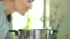 Young woman smelling aromas and testing the food in the kitchen, close up HD - stock footage