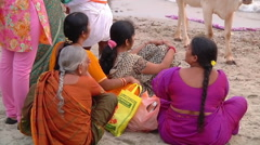 Tilt MS of cows and people on a beach in Rameswaram, India Stock Footage