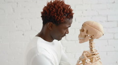 An insane black man wearing a straitjacket dance and looking at human skeleton - stock footage
