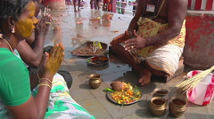 Tilt MS of people doing a ritual on an embankment in Rameswaram, India Stock Footage