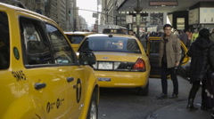 Asian man saying goodbye mother luggage and getting into yellow taxi cab NYC Stock Footage