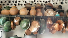 Copper and clay pots and pans hung in a kitchen Stock Footage
