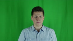 Young man sits thinking in front of greenscreen Stock Footage