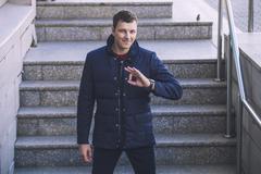 Male model in trendy modern youth warm jacket in the urban landscape - stock photo
