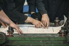 Men with drawings working in an old factory to install the equipment in helme Stock Photos
