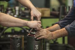 Male hands working spin parts in an old factory to install the equipment Stock Photos