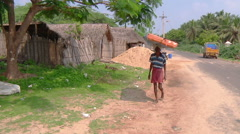 Pan MS of a man carrying a bid bag on his head in Rameswaram, India Stock Footage
