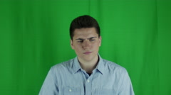 Young man sits thinking has an a-hah moment in front of greenscreen Stock Footage
