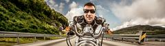 Funny Biker in sunglasses and leather jacket racing on mountain serpentine. - stock photo