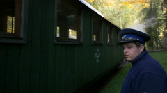 Train officer putting something between the wagon and locomotive, Mocanita - stock footage