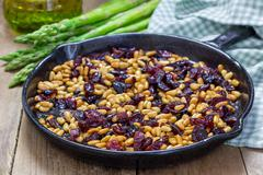 Roasted pine nuts with dried cranberries on a cast iron skillet. Ingredients - stock photo