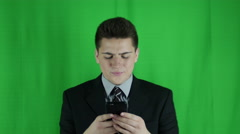 Young businessman works on phone looks up annoyed in front of a greenscreen Stock Footage