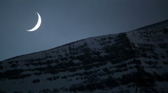 Crescent moon setting snowy mountain ridge clouds timelapse Iceland winter 4k Stock Footage