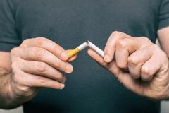 Quitting smoking - male hand crushing cigarette Stock Photos