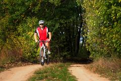 Man is cycling in autumn forest Stock Photos