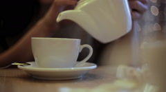 Woman pours hot water from the kettle into the cup Stock Footage