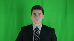 Young businessman flips of camera in front of greenscreen Stock Footage