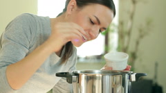Woman spicing soup with pepper and salt in kitchen, close up HD Stock Footage