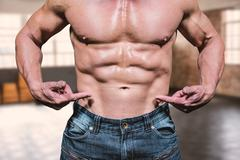 Composite image of midsection of shirtless man pointing at abs Stock Photos