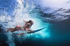 Underwater photo of girl with board dive under ocean wave - stock photo