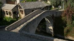 Kriva Cuprija over flowing water and a restaurant in Mostar, Bosnia-Herzegovina Stock Footage