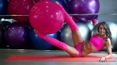 Beautiful girl in a pink suit raises kicked a ball for fitness Stock Footage