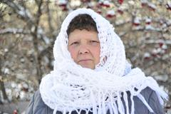 elderly woman in  white knitted shawl costs about Rowan - stock photo