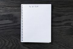 blank notepad with chequered pages on gray wood table with to do list phrase - stock photo