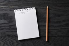 shopping list phrase in notepad on gray wood table - stock photo