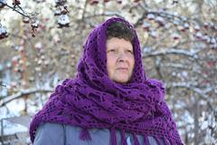 elderly woman in  purple knitted shawl on her head is about Rowan - stock photo