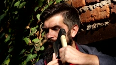 Bearded man with ax on a background of a brick wall with ivy Stock Footage