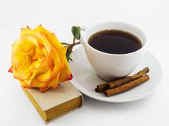 White cup of coffee, old book and yellow rose on white background Stock Photos