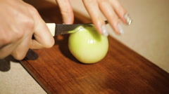 Woman cuts onion in the kitchen knife on a cutting board Stock Footage