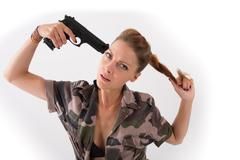 young sensual woman in military jacket looking at the camera with gun - stock photo
