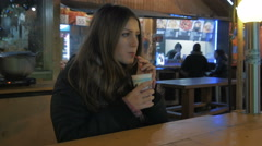 Young woman drinking hot drink at fair in the evening Stock Footage