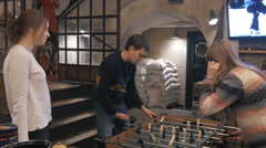 Group of young people having fun playing in table soccer in pub Stock Footage