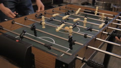 Friends having fun playing in table soccer in pub Stock Footage