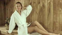 Girl in a bathrobe in a wooden sauna Stock Footage
