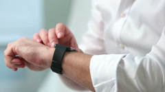 A man in a white shirt uses a smart watch. Close-up. - stock footage