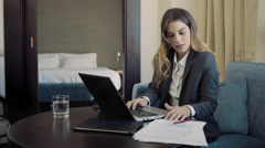Young business woman in hotel room working at day with laptop at a table Arkistovideo