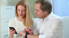 A young woman and a middle-aged man uses a smart watch and a smartphone. Stock Footage