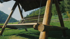 Beautiful wooden swing stands on a green grass Stock Footage