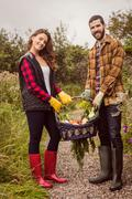 Couple posing while holding basket of vegetable Stock Photos
