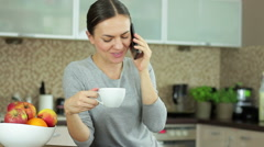 Young woman using her mobile phone in the kitchen at home HD Stock Footage