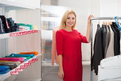 Portrait of beautiful saleswoman standing by rack in clothing store Stock Photos