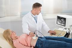Male doctor moving ultrasound transducer on pregnant woman's belly while look Stock Photos