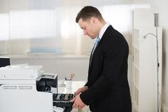 Side view of businessman adjusting cartridge in photocopy machine at office Stock Photos